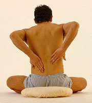 Photograph of a man sitting, reaching behind his back, and massaging his low back muscles.