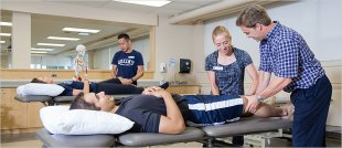 Physical Therapy students completing lower extremity exam. Back: Karen O'Neil (left), Nathanael Tsang (right). Front (from left to right): Jared Maynard, Emma Plater, Prof. Randy Booth. © Queen's University
